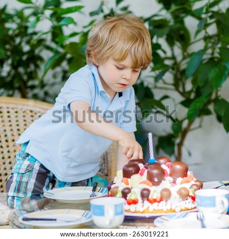 Funny blond boy celebrating his third birthday in home's garden with big cake. Happy child laughing about gifts and tasting cake. Child helping and serving table - stock photo