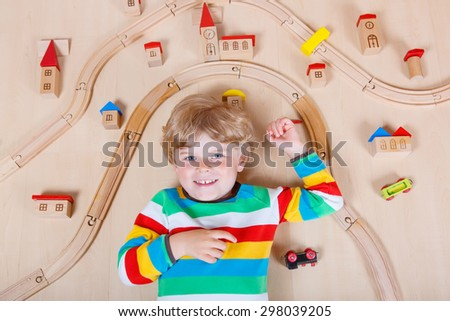 Funny blond child playing wooden trains and roalroad indoor. Active kid boy wearing colorful shirt and having fun with building and creating. - stock photo
