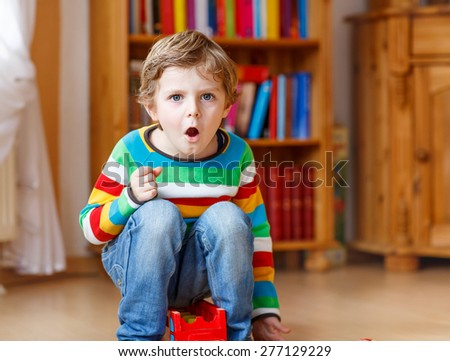 Funny blond kid boy shouting and playing, indoors. Child wearing colorful shirt. Portrait in a daycare. - stock photo
