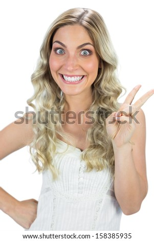 Funny blond model making peace and love sign on white background