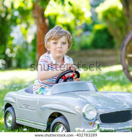 Funny blond preschool boy driving big toy old vintage car and having fun, outdoors. Active leisure with kids on warm summer sunny day. - stock photo