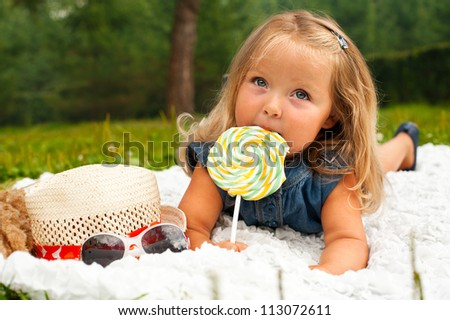 Funny blond toddler girl with lollipop lying on white plaid - stock photo