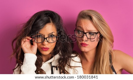 Funny blonde and brunette women portrait against pink background.  - stock photo