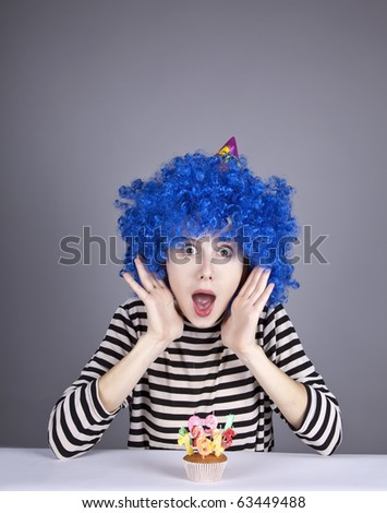 Funny blue-hair girl with cake. Studio shot.