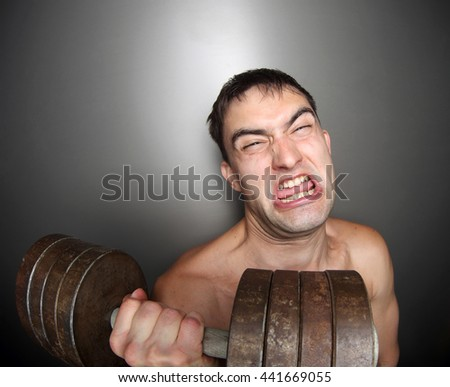 Funny bodybuilder with big dumbbell. Hard training. - stock photo