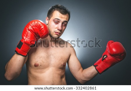 Funny boxer man in knockout over dark gray background. Comic weak fighter with red sport boxing gloves. Waist up humorous kickboxer - stock photo