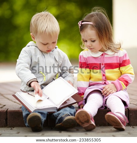 funny boy and girl reading book - stock photo