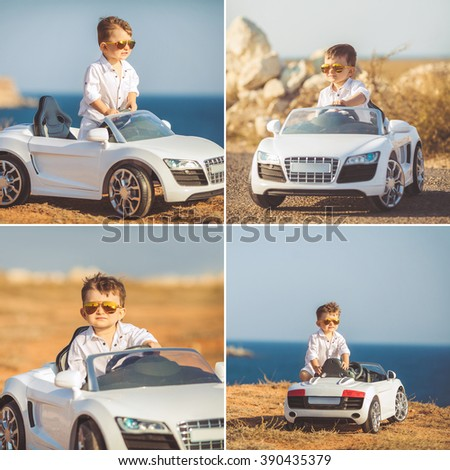 Funny boy car driver with the steering wheel. year-old boy in a white shirt in a red toy car in the street. Little boy driving big toy car and having fun, outdoors. Young kid portrait with toy car - stock photo