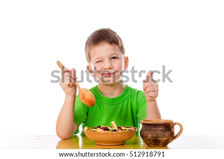 Funny boy eating oatmeal at the table, isolated on white