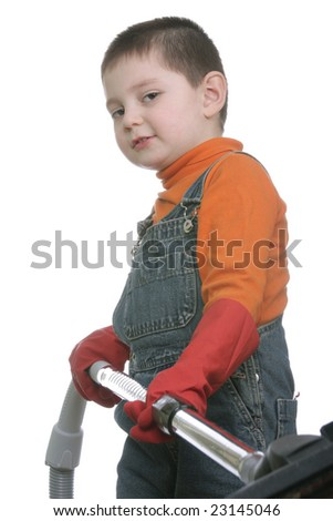 Funny boy in coveralls standing with vacuum cleaner hose over white