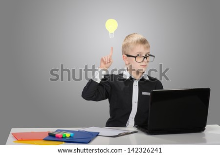 Funny boy raising the index finger up and looking at camera with drawn electric bulb - stock photo