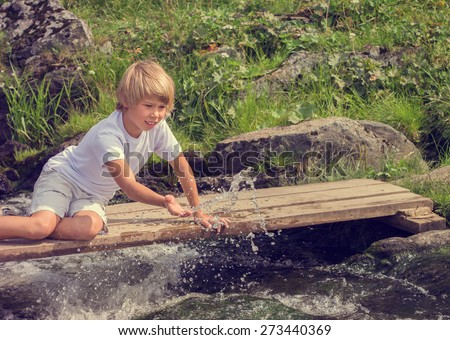 Funny boy splashes water sitting on a wooden bridge. - stock photo