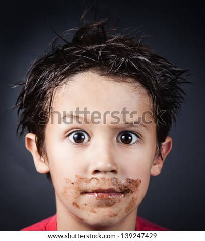 Funny boy stained with chocolate. - stock photo