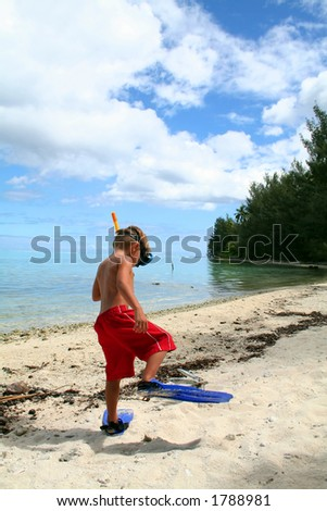 funny boy walking with fins on a sandy beach - stock photo
