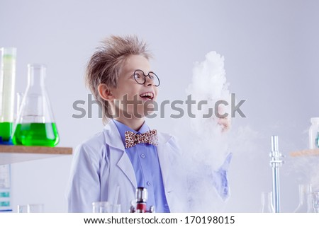 Funny boy watching reagent evaporation, close-up - stock photo