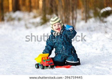Funny boy with toy car sitting on the snowy road - stock photo