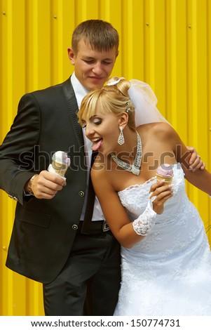 funny bride and groom eat ice cream yellow background - stock photo