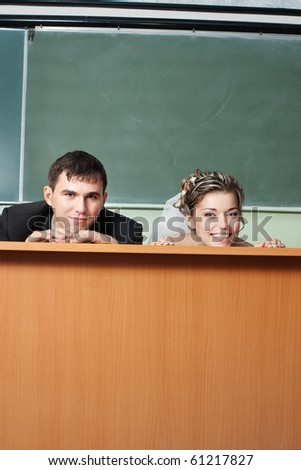 Funny bride and groom faces on classroom table with blackboard behind