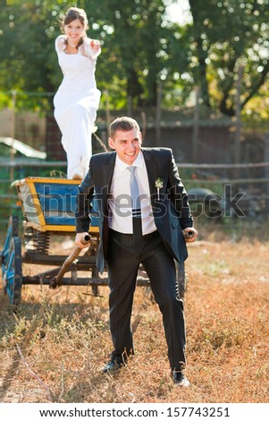 Funny bride and groom with cart outdoor - stock photo