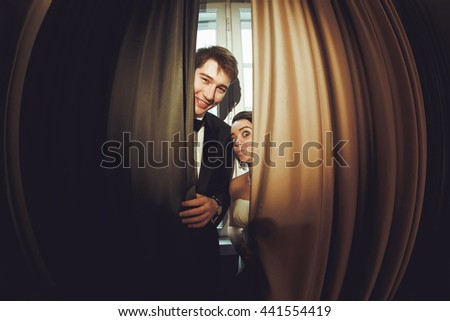 Funny bride stands behind a smiling groom hidden under the curtain - stock photo