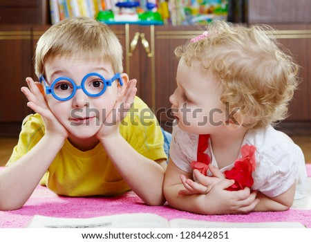Funny brother in toy glasses with baby sister on floor - stock photo