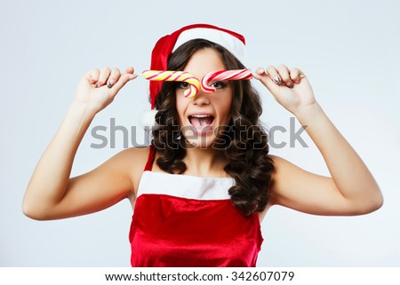 Funny brunette girl, with curly hair, wearing in red santa costume, posing with colorful candies in front of her face, on the white background, in studio, close up