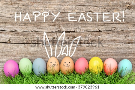 Funny bunny easter eggs decoration in green grass. Happy Easter! - stock photo