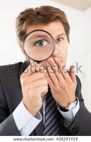 Funny business man holding magnifying glass portrait. Private detective investigation, layer, crime, business research or security concept Big eye through zoom lens. - stock photo