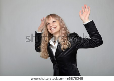 Funny business woman in a black suit with a gray background makes various hand gestures