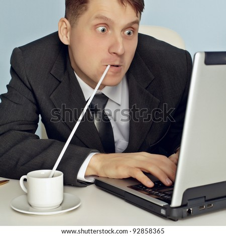 Funny businessman drinking coffee and working - stock photo
