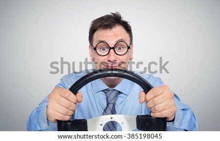 Funny businessman in glasses with a steering wheel, car drive concept
