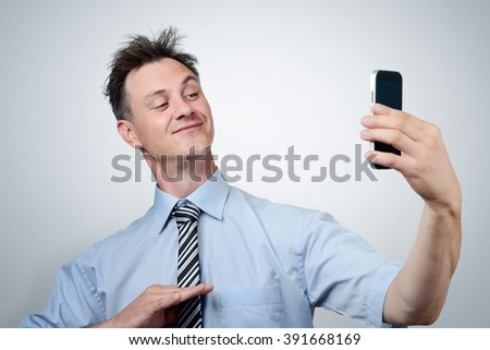Funny businessman photographing himself on a smartphone  - stock photo