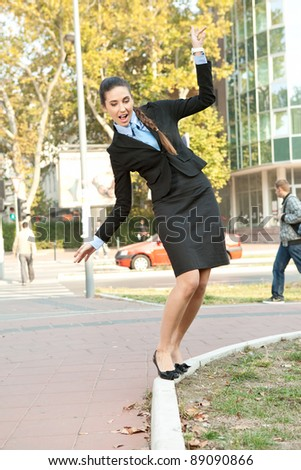 funny businesswoman balancing on  the curb, outdoor - stock photo