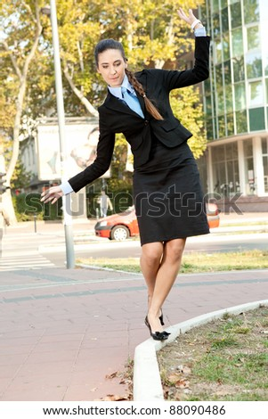 funny businesswoman trying to keep balance on the curb - stock photo