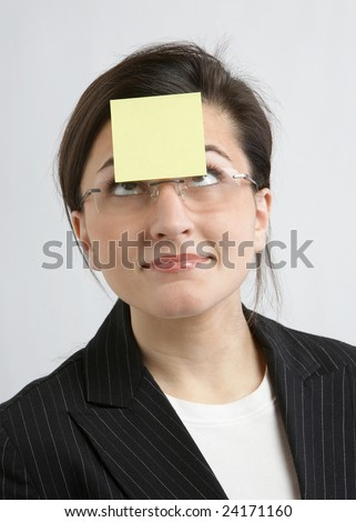 Funny businesswoman with yellow sticky note on forehead - stock photo