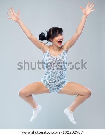 funny caucasian girl in pajamas jumping for joy - stock photo