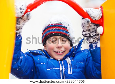 Funny cheerful boy in jacket and hat playing outdoors in winter sliding. Winter vacation concept.  - stock photo