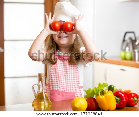Funny chef girl preparing healthy food at kitchen - stock photo