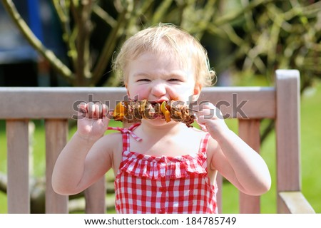 Funny child, adorable blonde toddler girl in red dress messy around mouth eating delicious meat made on bbq sitting outdoors in the garden on a wooden chair on a sunny summer day - stock photo