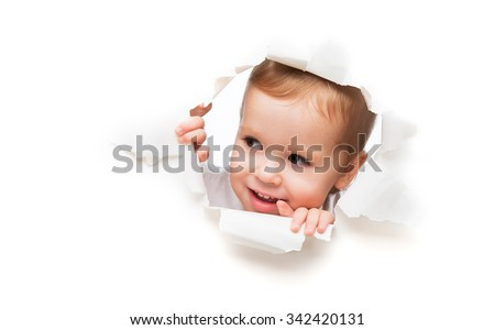 Funny child  baby girl  peeping through a hole in an empty white paper poster - stock photo