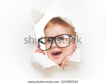 Funny child  baby girl with glasses peeping through a hole in an empty white paper poster - stock photo