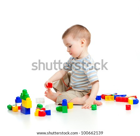 funny child boy playing with construction set over white background - stock photo