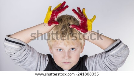 Funny child boy with hands painted with colorful paint like Spain flag - stock photo