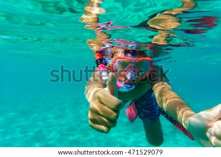 Funny child diver in sea with mask swimming underwater.