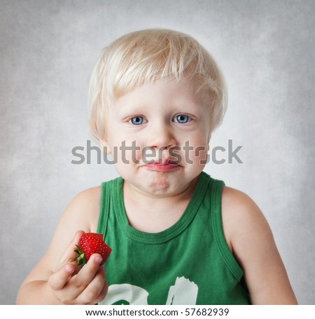 Funny child eats strawberries.Age 2 years. - stock photo