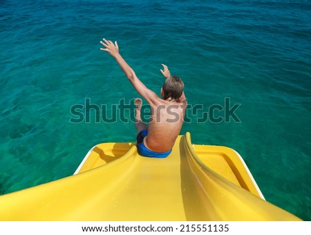 Funny child enjoying summer vacation sliding from a water catamaran  - stock photo