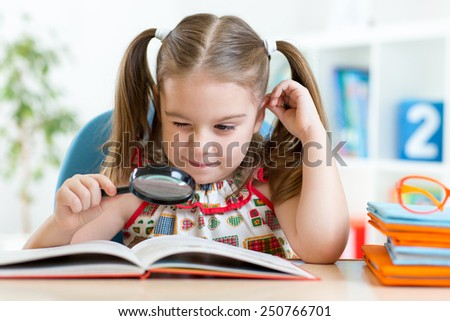 Funny child girl reads book using magnifier while sitting at table at home