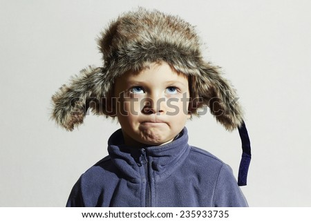 funny child in fur Hat.fashion casual winter style.little boy in blue sport sweater.children emotion - stock photo