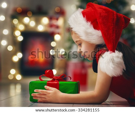 Funny child in Santa red hat holding Christmas gift in hand.  - stock photo