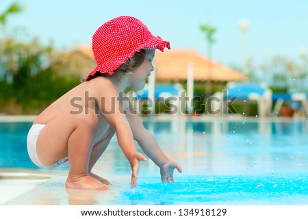 Funny child in sunhat have a fun with a splash near swimming pool - stock photo